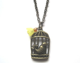 Brass Pendant Necklace. Bird outside a Cage adorned with Yellow flower. 21 inch brass chain.