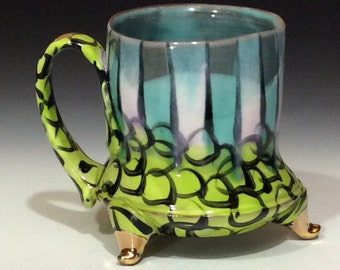 Green and white stripes with lime green and black circles and gold footed mug