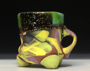 Bright colorful yellow and lilac with copper green glaze with gold luster dots and white inside and hollow feet