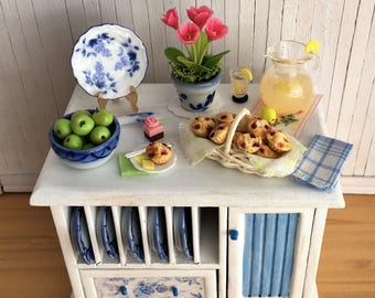 Miniature Kitchen Island With Plate Rack Filled With Blue And White Plates, Blueberry Muffins, Bowl Of Green Apples, Lemonade, And More