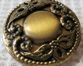 """Vintage ornate, metal button, 1"""" open work top, brass toned, central 'mound'. Top stretched over metal back with self shank. UNK17.2-18.18."""