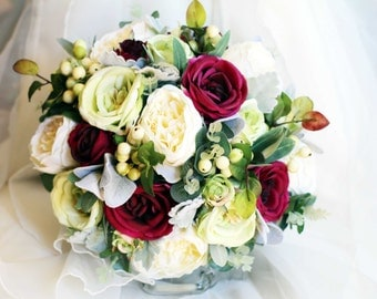 Romantic wedding bouquet.  Peonies, garden roses, berries and lush foliage in shades of soft green, plum, cream and grey bouquet.