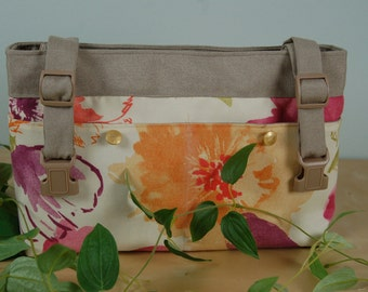 Powerchair - Walker bag in a Refreshing Floral print, with a tan lining and gold accent buttons.