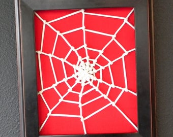Framed white web over red fabric