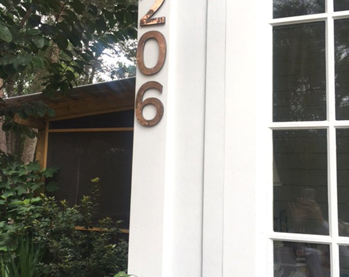 "Large block house numbers 6""/150 mm in copper,  Antigoni font, polished and mounted on cladding with sign locator fittings"