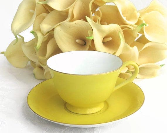 Noritake cup and saucer, bright cheery yellow with white inside cup and gilt trim, made in Japan, mid 20th century