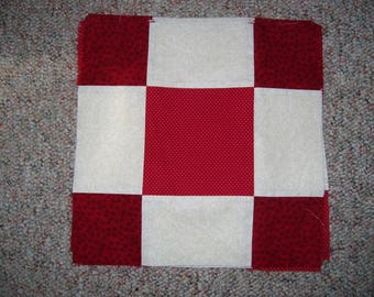 13 finished quilt blocks made with one off white fabric and 2 different red fabrics