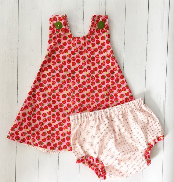 Baby girls strawberry print dress by Monnalisa Bebé. The dress fastens down the back with buttons and has a pink and white grosgrain ribbon sash that is embellished with diamanté beads. It is fully gathered at the waist, and has a cotton lining with a tulle frill.