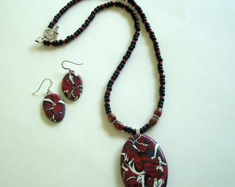 Red, Black, and White Abstract Oval Polymer Clay Pendant with Beaded Necklace and Matching Earrings by Carol Wilson of PollyClayDesigns