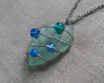 Real sea glass necklace/pendant, wrapped with blue beads and wire, clear glass