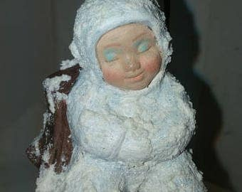 Snow Baby Ornament Beside Stump