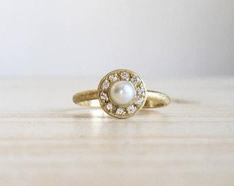 Anello sottile con piccola perla e contorno di brillanti.