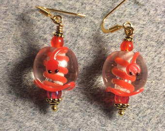 Clear and red lampwork coiled snake bead earrings adorned with red Czech glass beads.