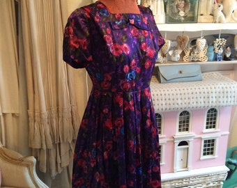 1950s floral satin dress in purple and red, with bow