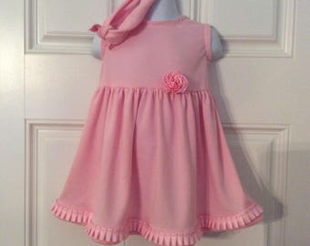 Pink toddler knit dress, empire waist with a gathered skirt. Sweet ruffled rose at the waist. Matching stretchy headband in the same knit.