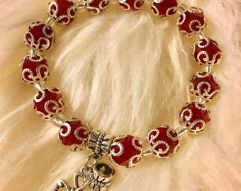 Red bracelet with a cross charm