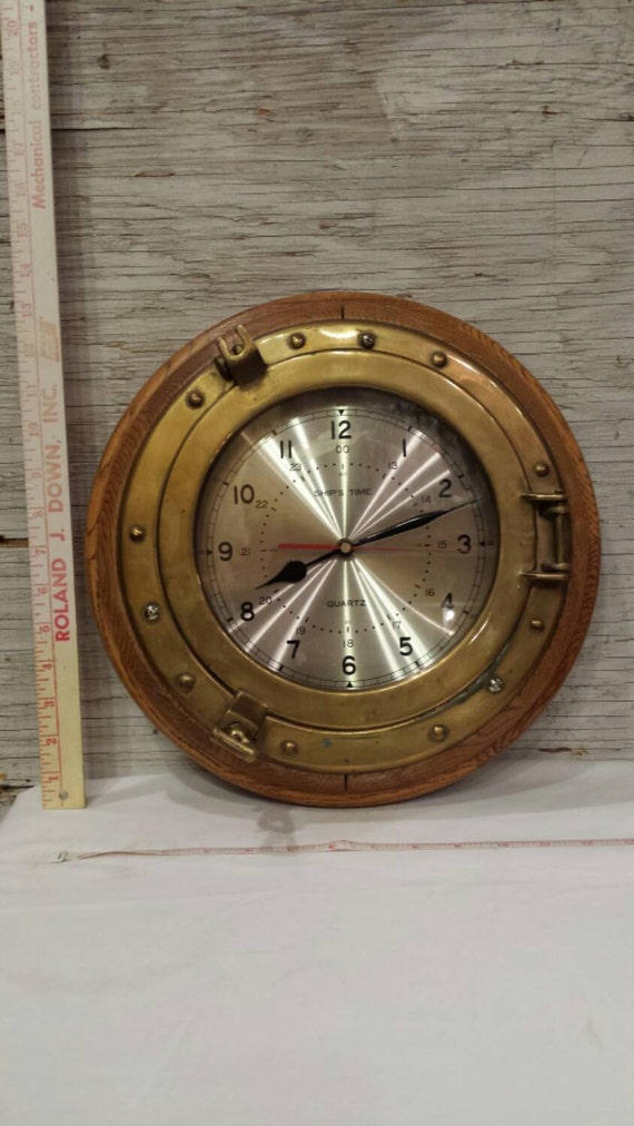 Vintage Ships Brass Porthole Window Converted into a Functional Wall Clock. Working Condition. Oak Back.  Nicely Done. A Nice Gift Idea.