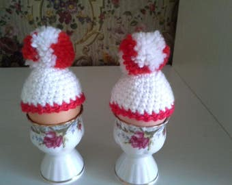 crocheted white egg cosy with PomPoms, set