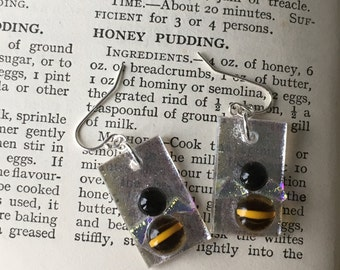 Fused glass bee earrings on a silver background