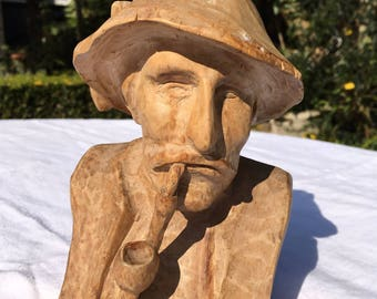 Hand carved wooden figure of a man smoking a pipe