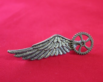 Gear and wing brooch