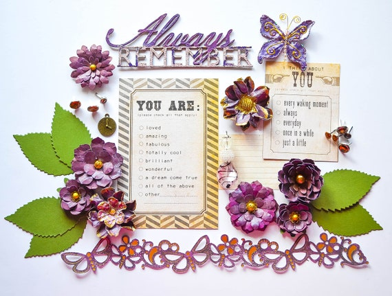 This pretty purple and plum kit, set against gold, contains everything you need for multiple layouts: 10 12x12 cardstock/papers, journal spots, metal brads and embellishments, lampwork glass bead dangle, die cut butterfly border with gold foil accent, die cut leaves, a beautiful butterfly, and a heat-embossed Blue Fern Studios title: Always Remember.