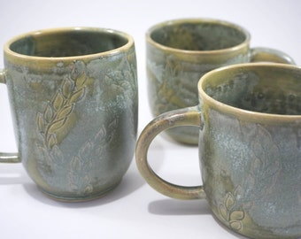 Coppery green mugs with leaf decoration