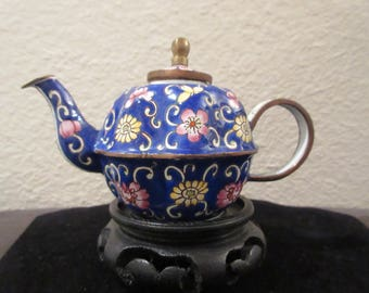 Gorgeous minature Teapot by Kelvin Chen. This is a high quality item featuring a cobalt blue background with pink and yellow floral design.