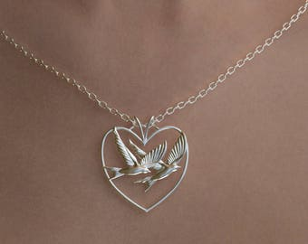 Heart motif sterling silver pendant holding two birds flying together