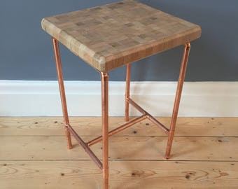 Side table in a retro industrial style with a copper pipe frame and reclaimed oak butchers chopping block style top