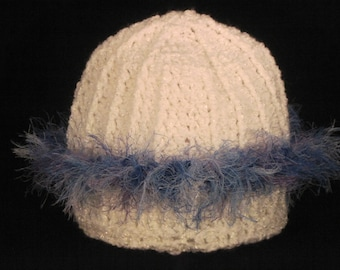 soft, white child's hat with blue and purple fringe