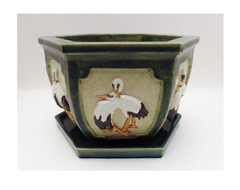 A handmade stoneware planter / plant pot with high relief decoration of storks