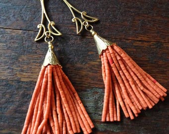 Orange beaded tassel earrings on a brass deco pendant.