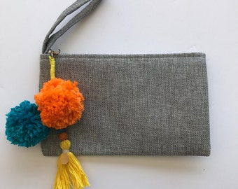 Gray makeup bag with pom poms and tassels
