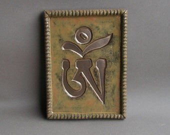 Om (Tibetan version) imprinted in gold on a stoneware hanging tile