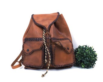 vintage 60s 70s rustic leather backpack bag dark brown stitching pockets drawstring rucksack distressed age shoulder straps pack hippie boho
