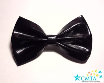 One black faux leather hair bow. Portion of sale goes to charity. Cruelty-free.