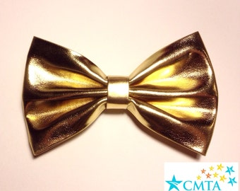 One gold faux leather hair bow. Portion of sale goes to charity. Cruelty-free.