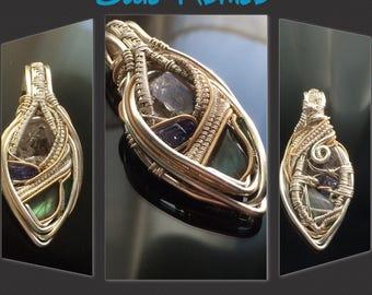 "It's named ""Blue Romeo"" - Silver wire-wrapped pendant by Crystalchemy.  W/ black carbon enhydro quartz, tanzanite, labradorite, and indicoli"
