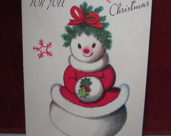 Colorful unused 1950's Rust Craft christmas gift card shows a snow lady dressed up in red and white dress, holly berry muff,pine tree hat