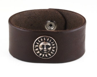 Wide thick leather bracelet cuff wristband with sun face concho.
