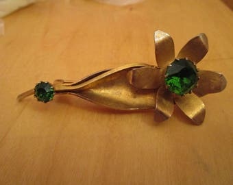 "vintage  goldtone flower with two deep green stones in good condition 3""high"