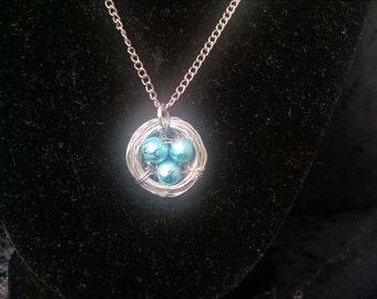 Bird's nest necklace, shiny blue eggs