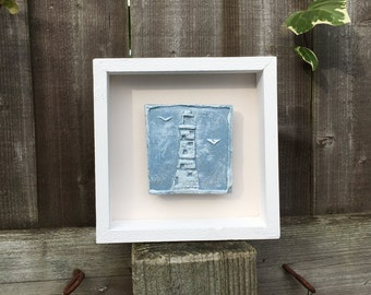 Framed original wall art, clay impression of a lighthouse, seaside. Blue and white in a white wooden box frame.