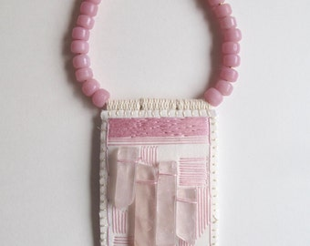 Rose quartz pendant abstract hand embroidered with pale pink colors on a thick gold leather cord with pink Native American crow beads