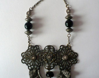 Unique piece of jewelry with a vintage filigree ornament of metal and crochet roezel in old grayscale