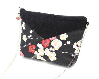 A small black shoulder bag patterned with pink and white flowers