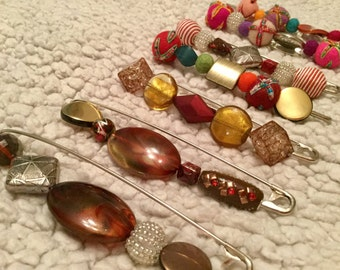 Browns, golds, reds, orange,sunset coloured brooches