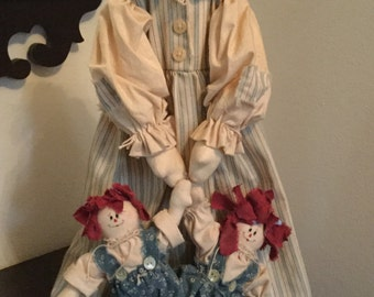 Folk art doll holding Raggedy Ann and Andy