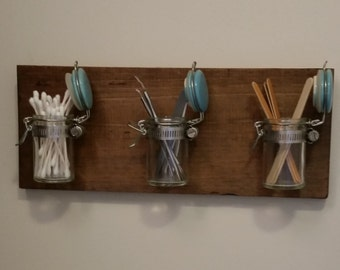 Wooden wall hanger with small jars